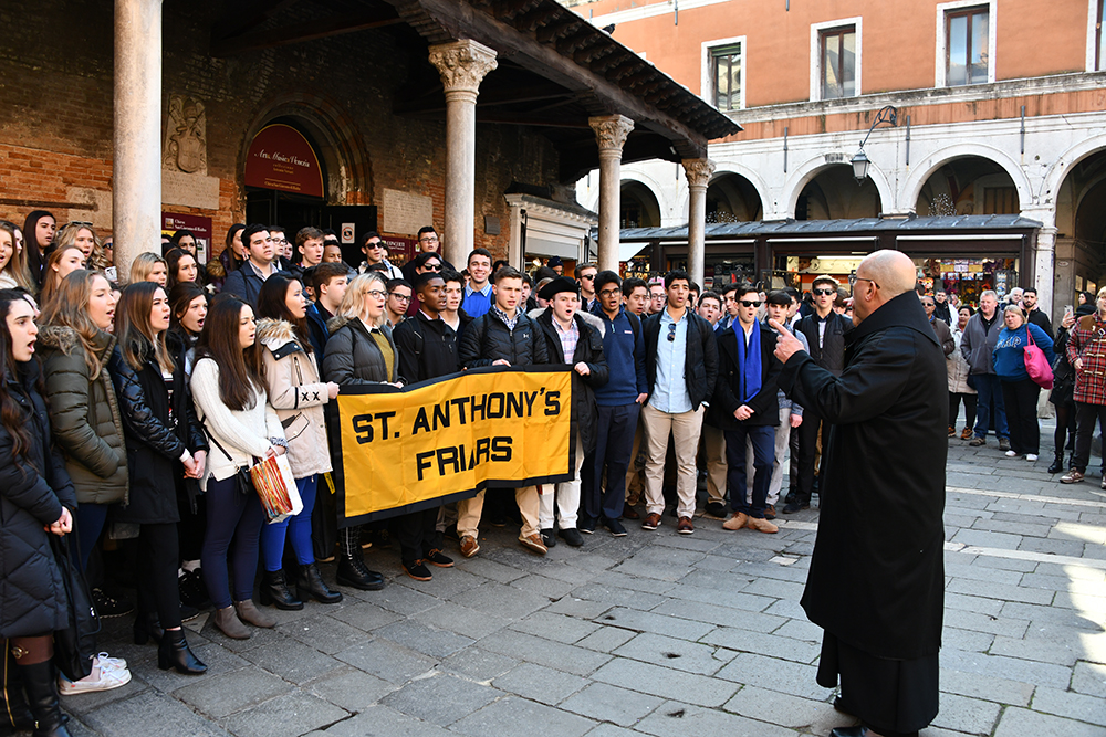 A conductor standing in front of group of students singing in an Italian city square.