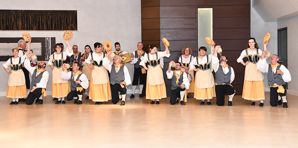 Twelve dancers wearing traditional Italian folk costumes.