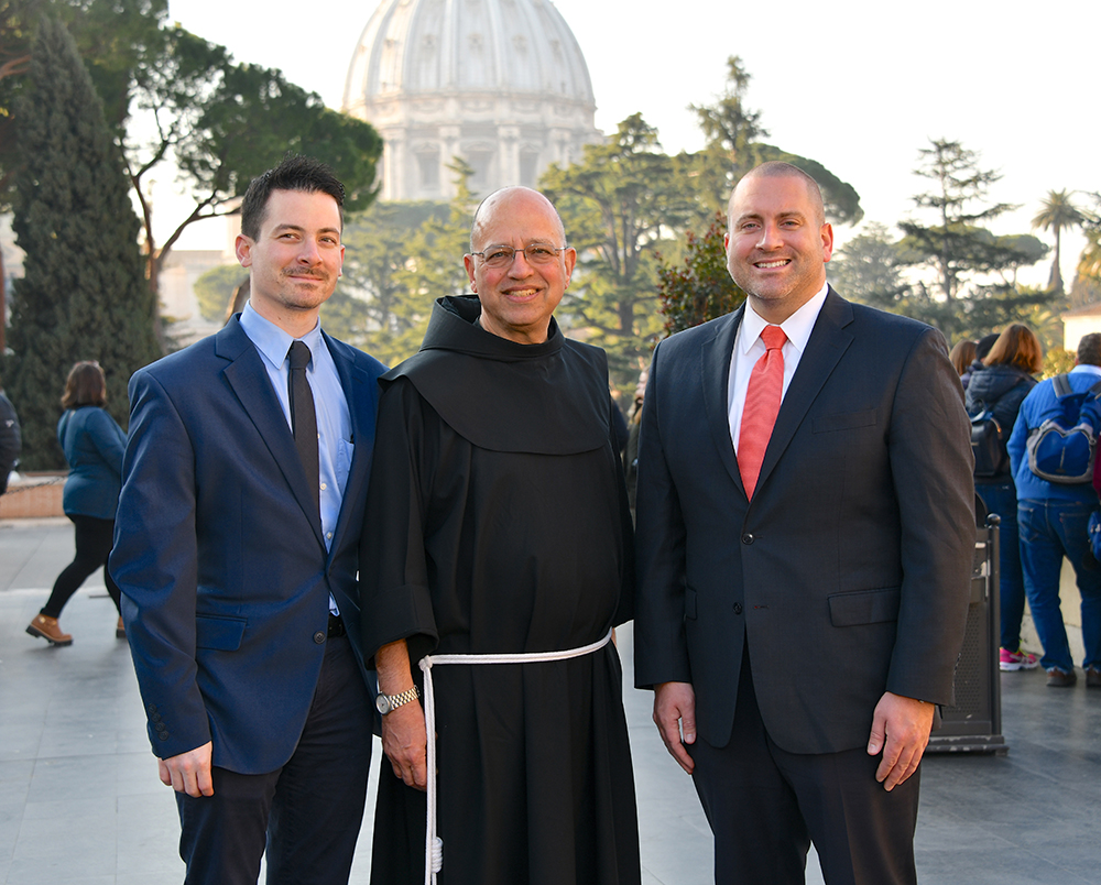 Three people standing in an Italian square, two wearing suits and one wearing a monk's robes.