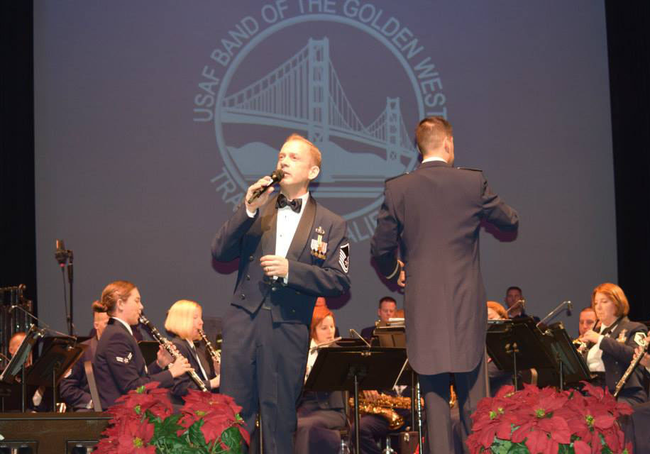 A person in a military band tuxedo speaking into a microphone in front of a military band performing.