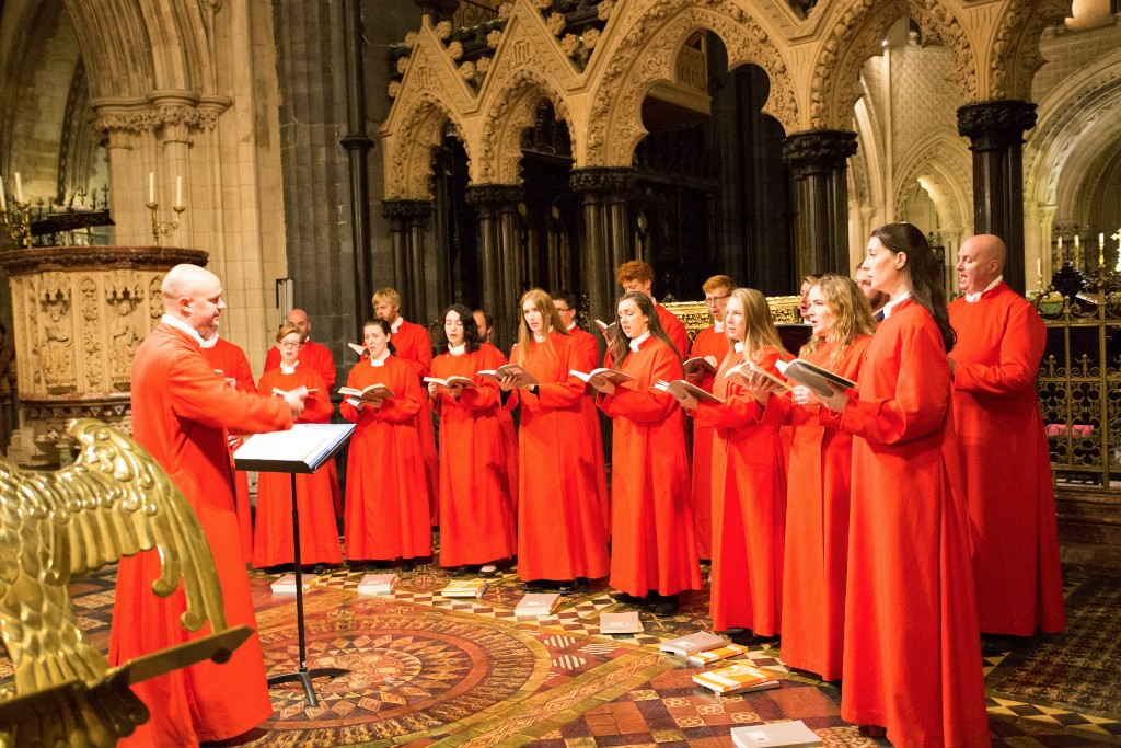 A direector conducts members of the Choir of Christ Church Cathedral. They are all wearing red, floor-length robes.