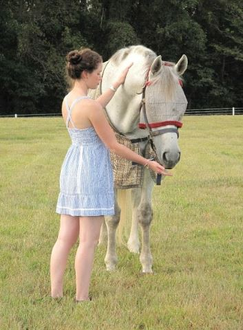 Laila Verhoeff stands next to a white horse