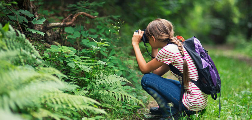 A female student taking a picture of nature as part of a competency-based education learning initiative.