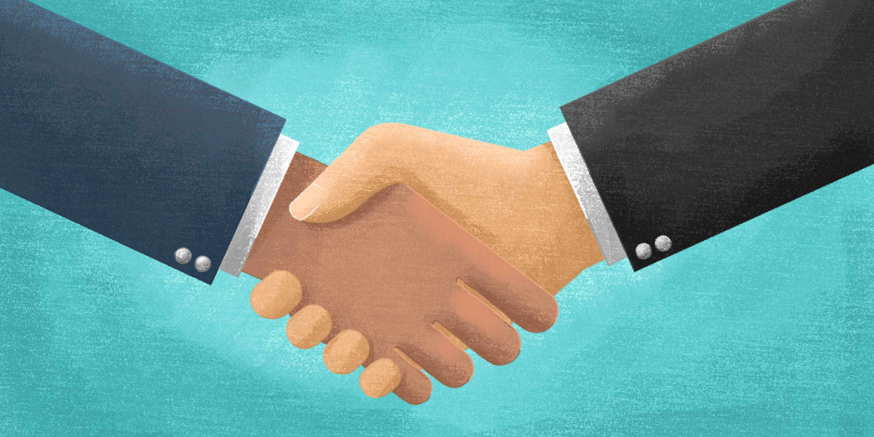 two business professionals shake hands in partnership