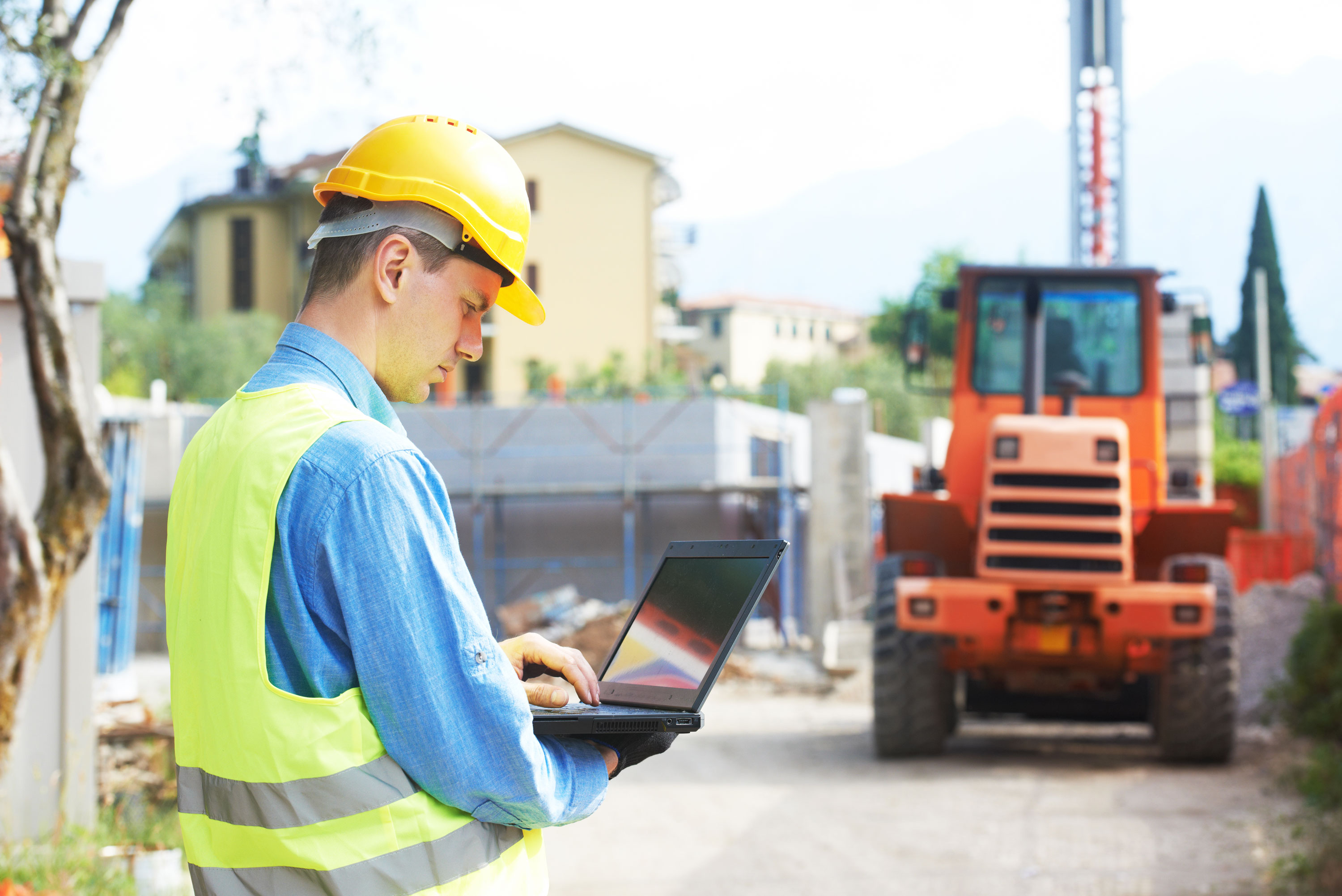 construction site foreman uses a computer on the job