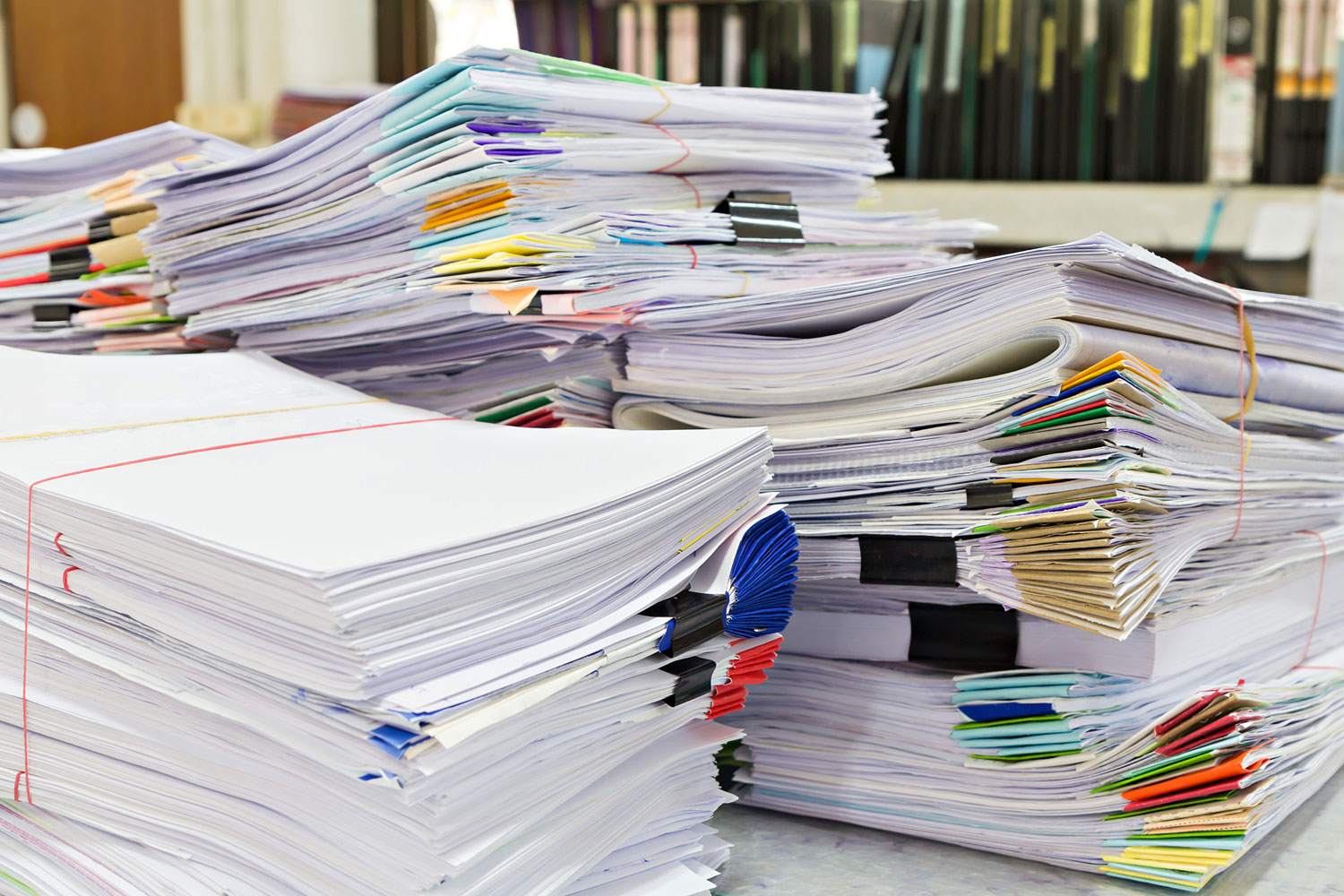 stacks of invoices and paper payments on a desk in AP