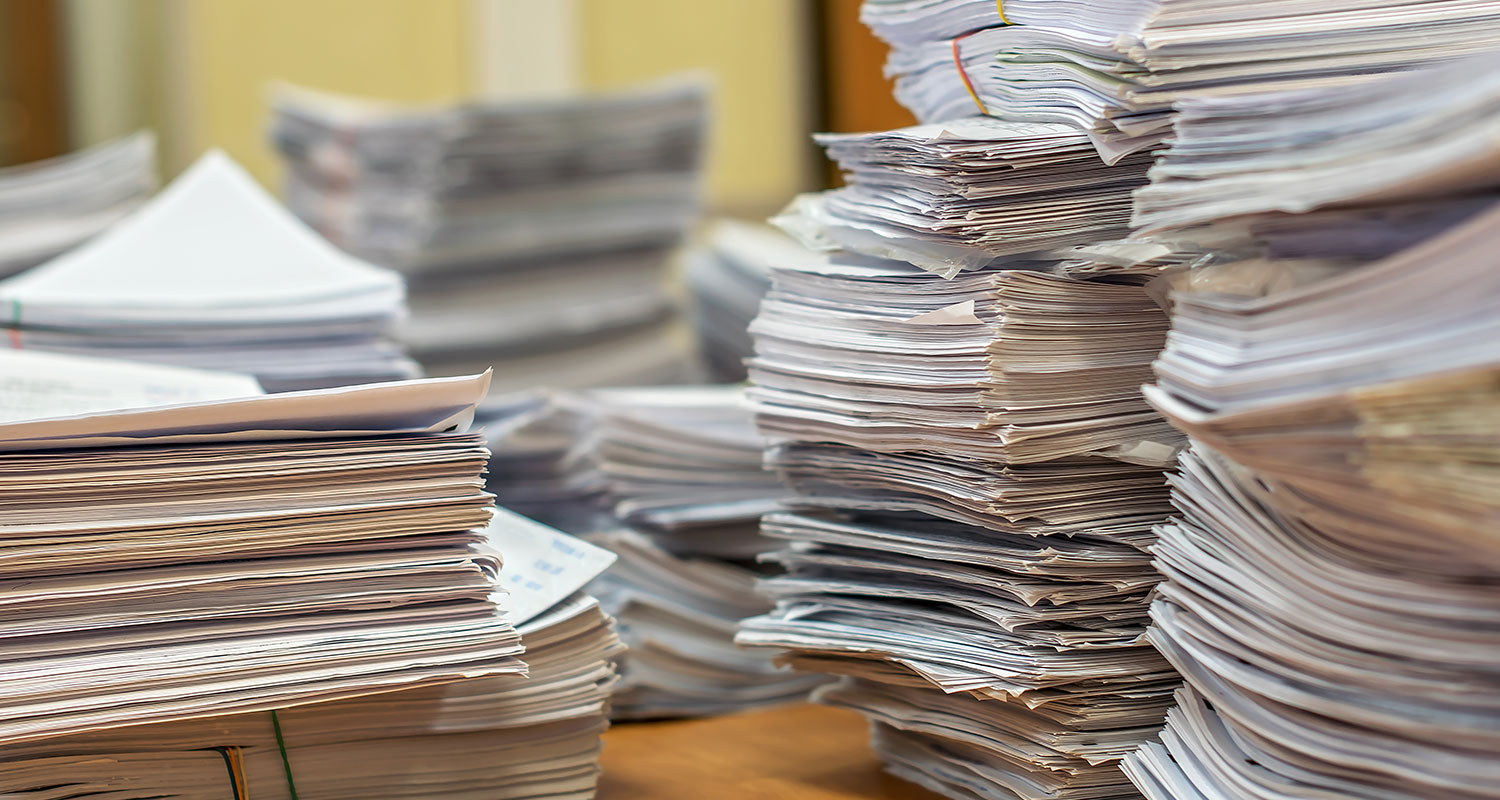 stacks of paper files on a construction AP specialist's desk
