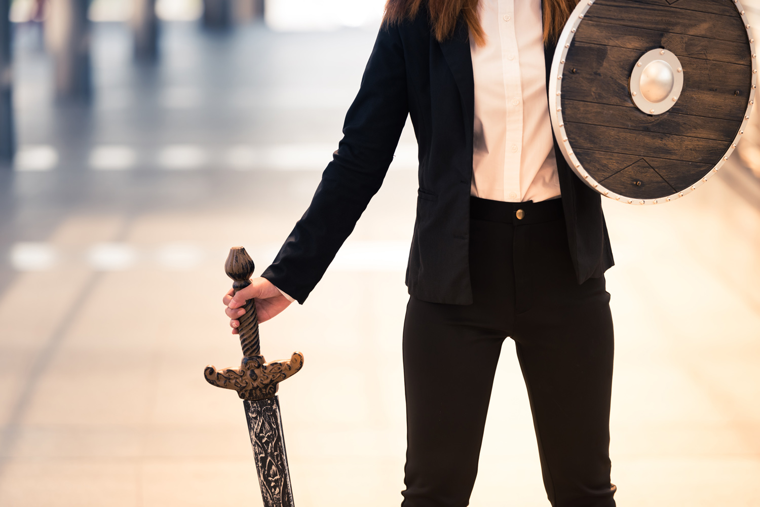 businesswoman stands with shield and sword in defense of data