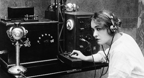 black and white photo of a woman operating a telegraph machine