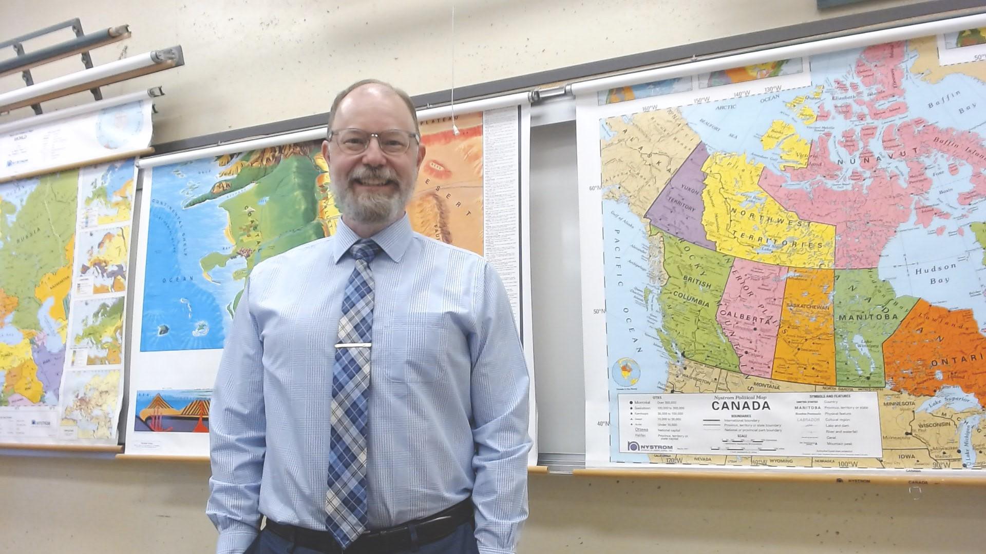 Homme debout devant des cartes dans une salle de classe.