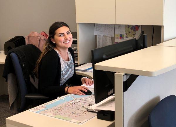 Femme souriante, assise à un bureau.