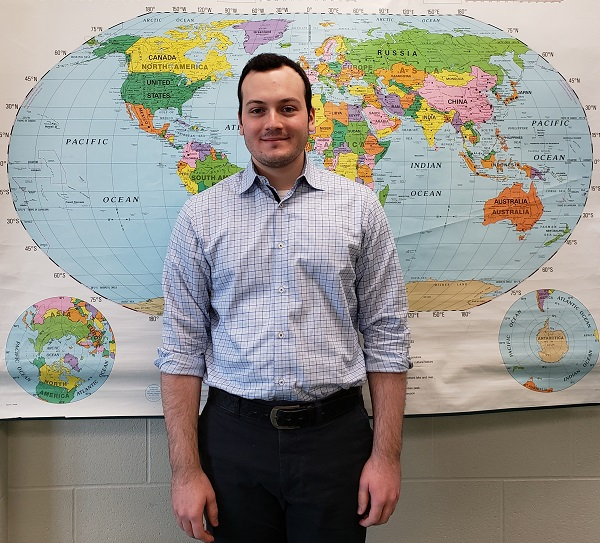 Young man standing in front of a wall map of the world.