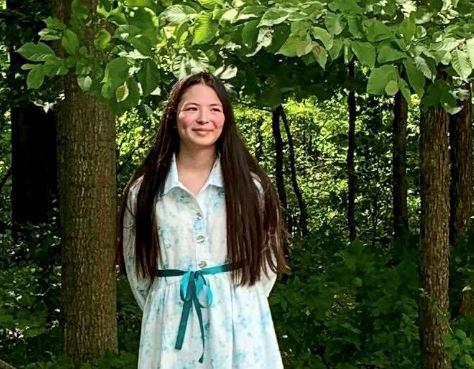 A teenaged girl smiling.