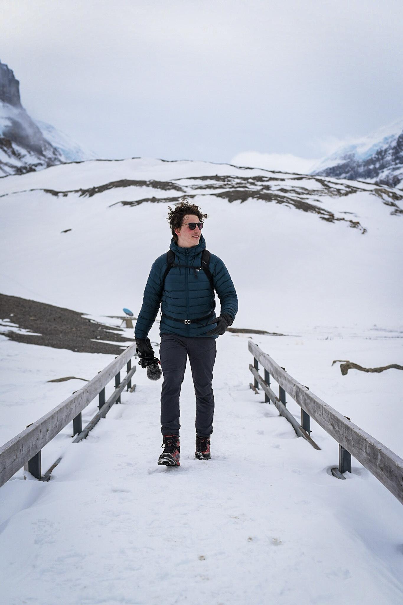 Ian Ladd walking along a bridge near a glacier. Holding his camera in his right hand.