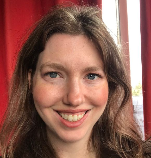 Image d'une femme aux cheveux foncés qui sourit.