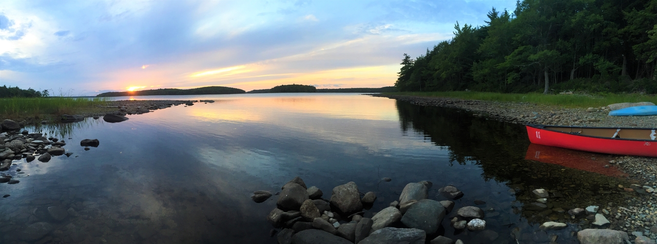 View of the sunrise over a lake near a campsite in Kejimkujik National Park.