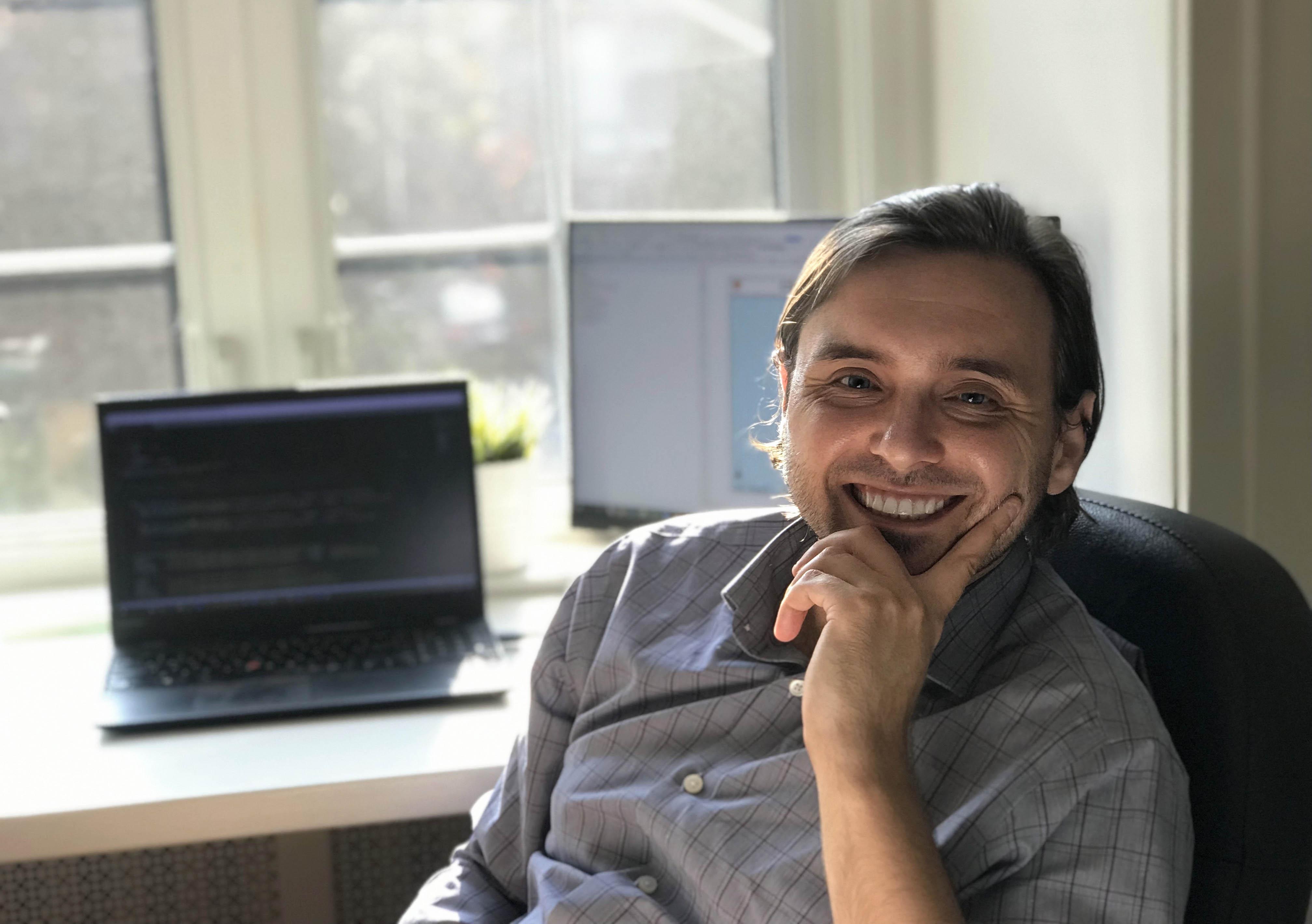Homme souriant, assis à un bureau.