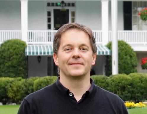 Homme aux cheveux bruns courts souriant dans une chemise noire.