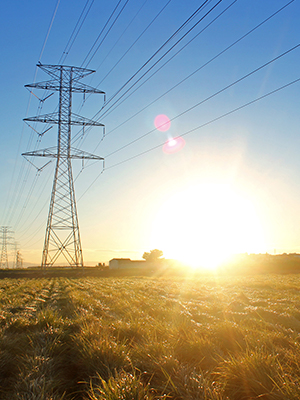 sole che splende vicino a torri elettriche