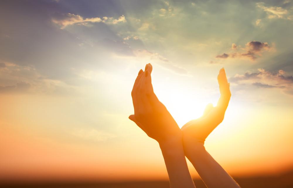 mani a coppa che reggono il sole