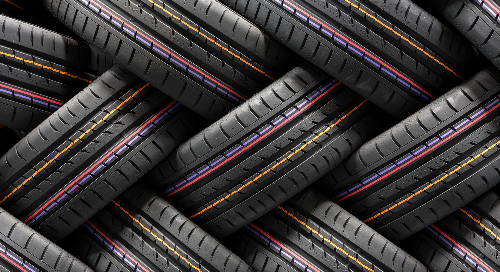 Closeup of tires with some colorful lines between rows of treads.