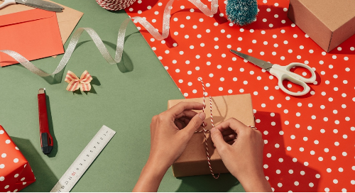 Gift-wrapping scene with a woman's hands wrapping a small box, with wrapping supplies strewn on the table top.
