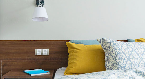 view of nightstand next to large bed with fluffy yellow and blue pillows