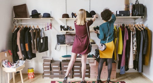 Rear view of two women handling merchandise in a fashion apparel showroom.