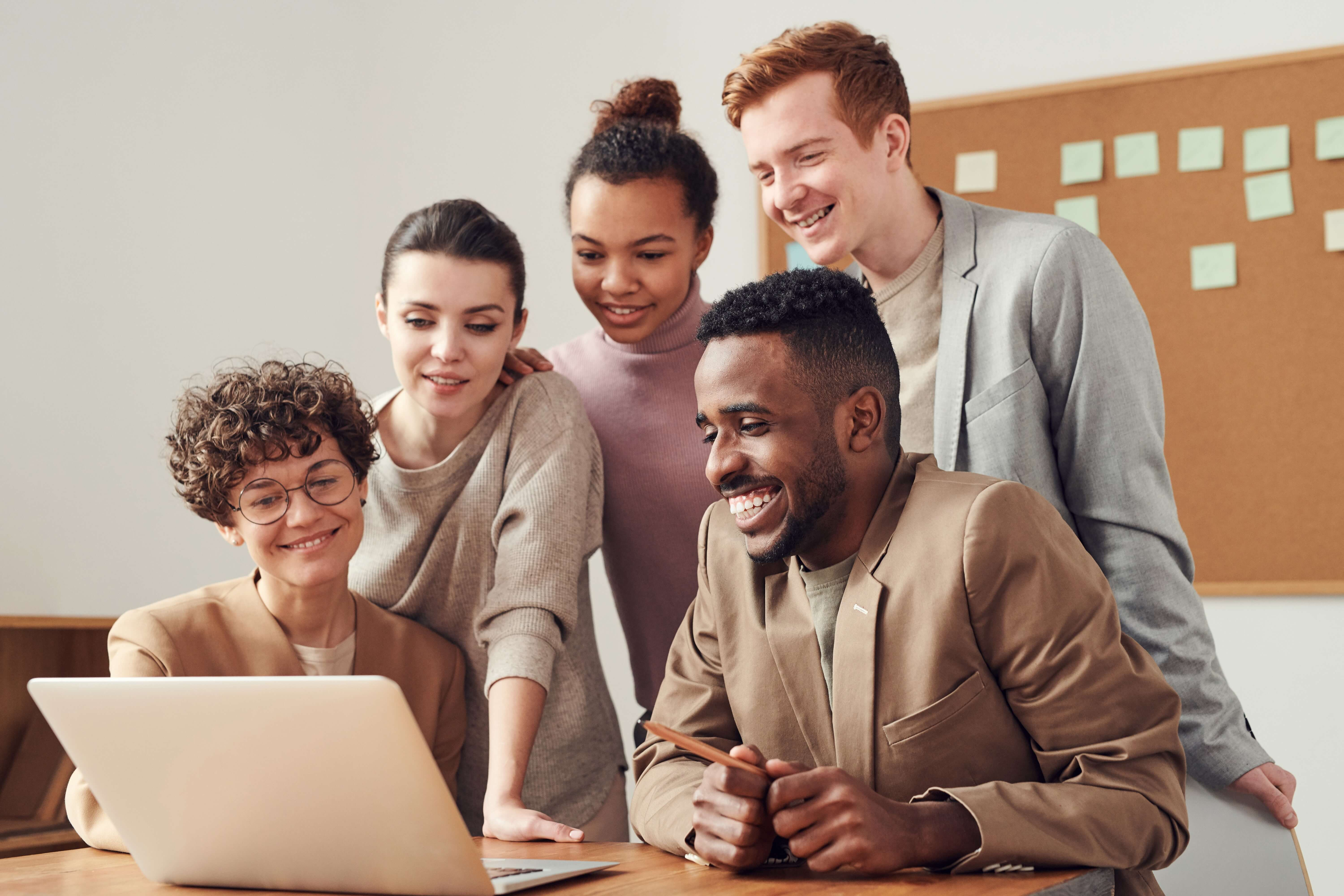 group of employees looking at laptop