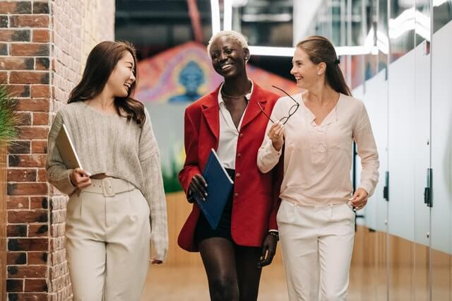 three women walking and laughing in an office
