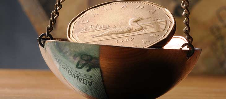 A canadian dollar in a suspended copper bowl.