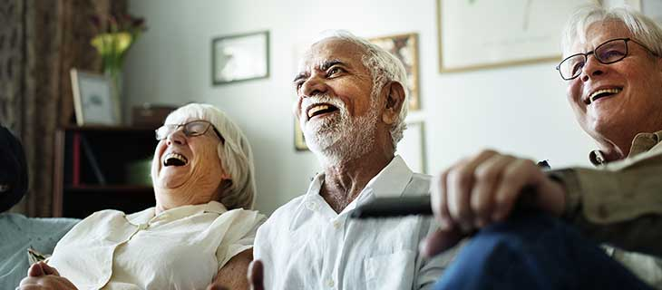 An older aged groupe on a couch laughing.