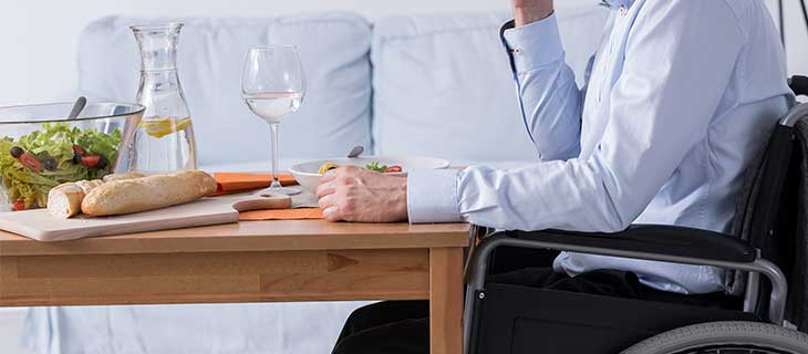 A man in a wheelchair at the table eating a salade with a glass of white wine.