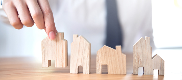 Close up of young man's hands moving pieces of toy houses