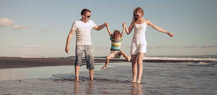 Mother, father and child holding hands lifting child into the air while standing in the ocean.