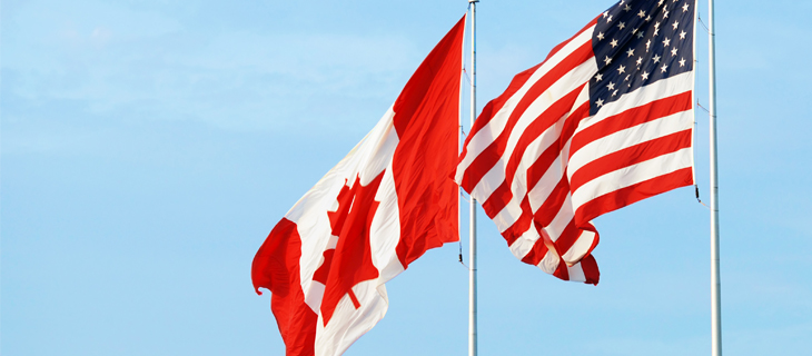 Canadian and United States flags blowing in the wind.
