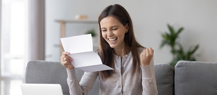 A happy student holding a document in her hand.