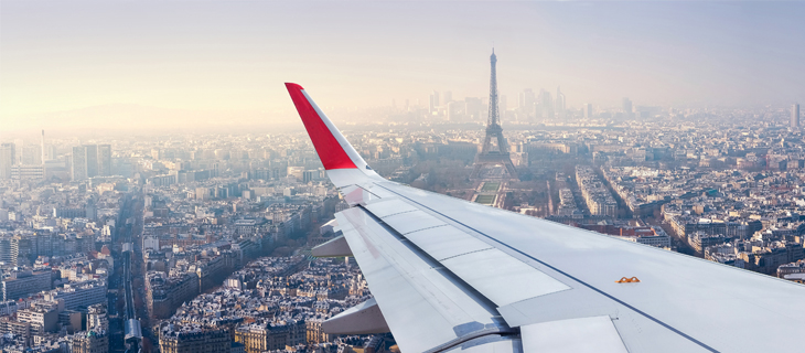 The left wing of a plane over looking Paris.