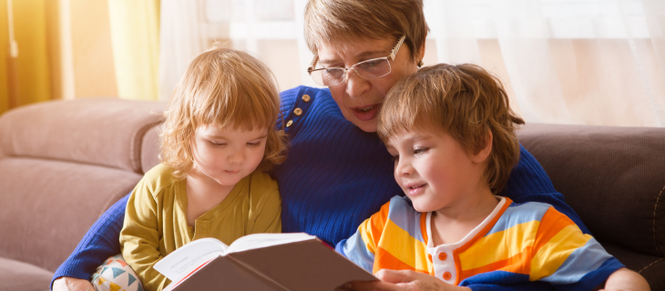 Grandmother reading from a story book to her two grandchildren