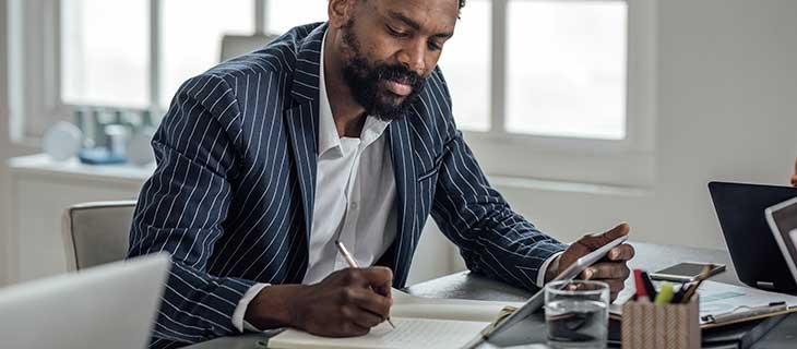 Un homme mature tenant une tablette signant des documents.