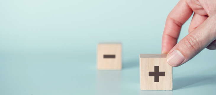 Close-up of man's hand holding wooden blocks with addition and subtraction symbols.
