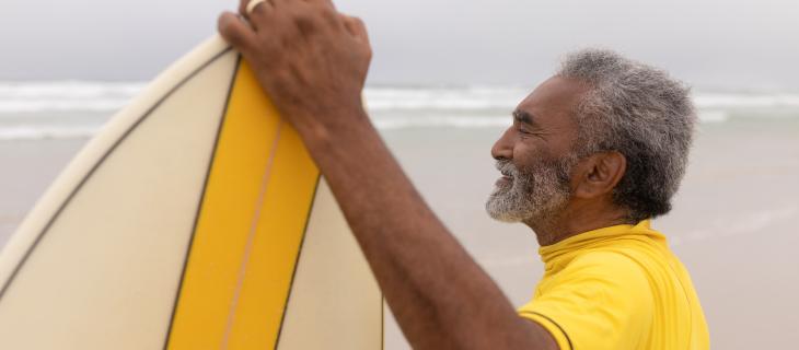 Un homme plus âgé souriant tout en tenant une planche de surf.