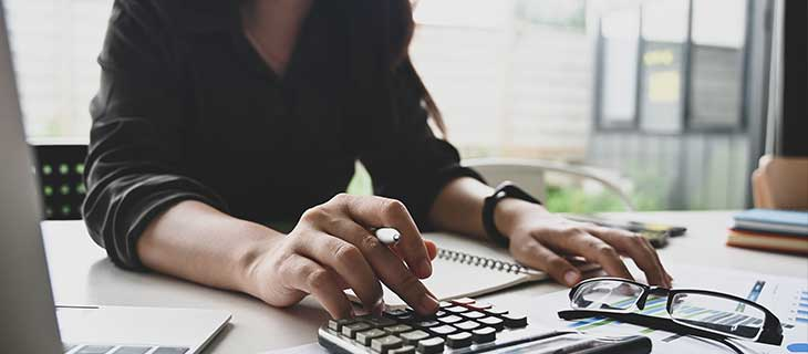 A woman at a desk using a calculator to do paperwork.