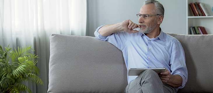 Un homme  assis sur un canapé tenant une tablette et regardant de côté.