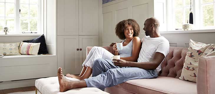 A couple smiling and snuggling on a couch and sipping coffee.