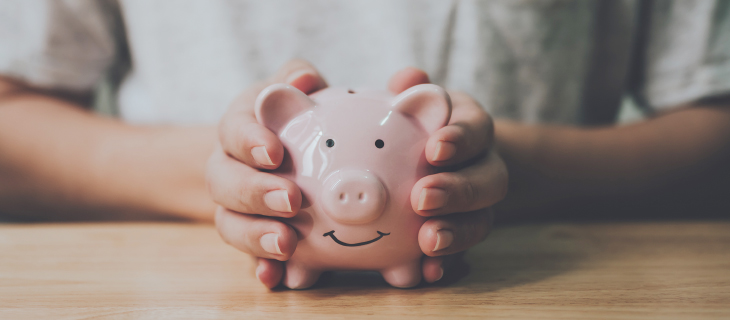 Two hands holding a smiling piggy bank.