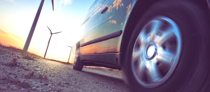 A panoramic view of a car driving by a windmill farm.