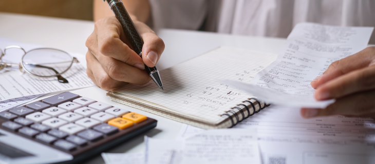 A person holding a pen and using a calculator whilst doing their taxes.