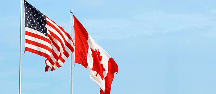 United States and Canadian flags next to eachother flowing in the wind.