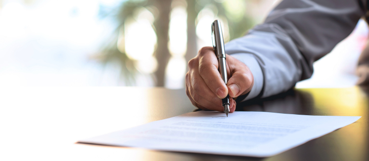Man signing documents with a fountain pen.